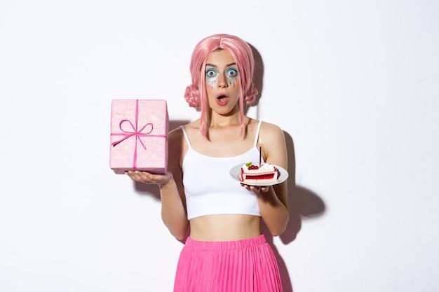 Retrato de niña hermosa sorprendida en peluca rosa, recibir regalo de cumpleaños, sosteniendo el b-day cake y sonriendo feliz, de pie.