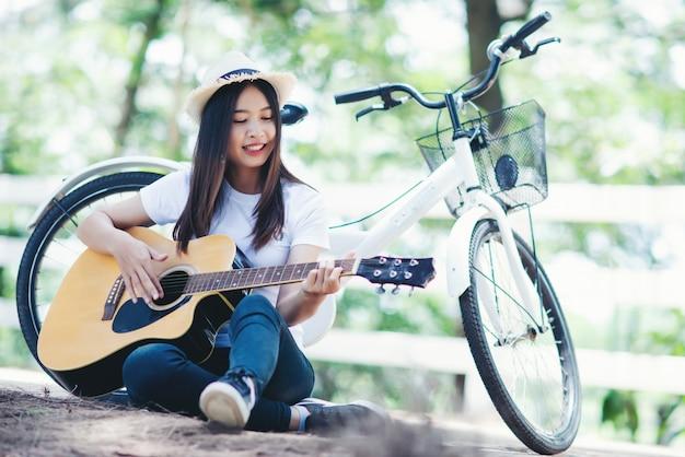 Retrato de niña hermosa tocando la guitarra con bicicleta en la naturaleza