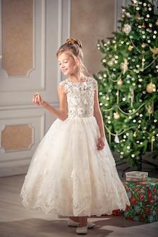 Retrato de una niña con un hermoso vestido sobre un fondo del árbol de navidad