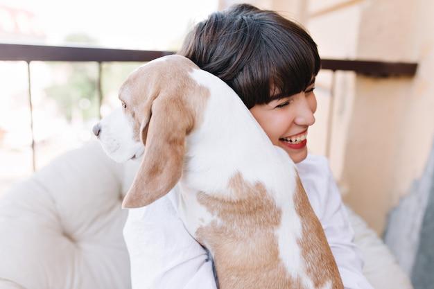 Retrato de niña increíble riendo, mientras abraza al perro beagle mirando a otro lado
