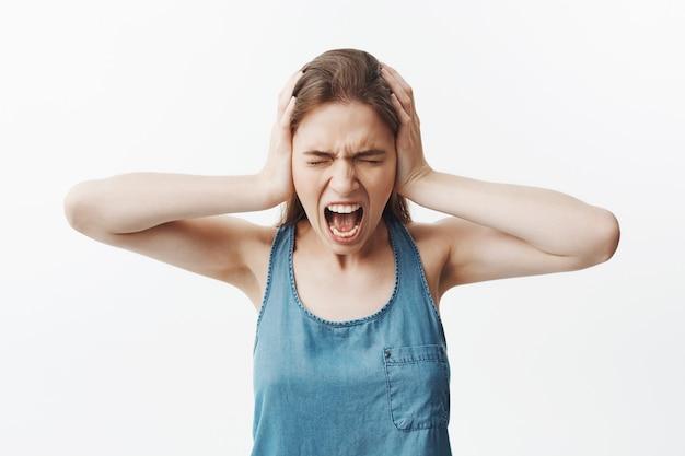 Retrato de niña infeliz morena joven estudiante en camisa azul cerrando los oídos con las manos, gritando en voz alta por el dolor de cabeza, de pie con los ojos cerrados, cabreado ruidos fuertes en el piso vecinos.