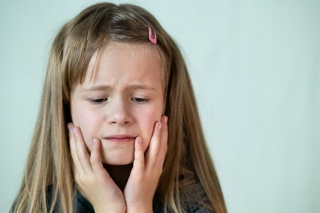 Retrato de niña infeliz que cubre su rostro con las manos llorando.