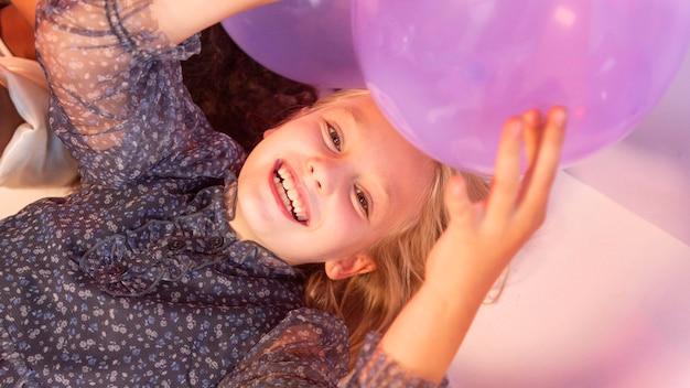 Retrato, niña joven, en, fiesta, con, globos