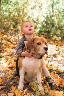 Retrato de niña jugando con perro beagle en bosque