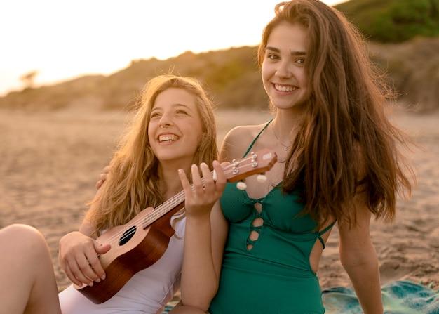 Retrato de niña jugando ukelele con su amiga en la playa de arena