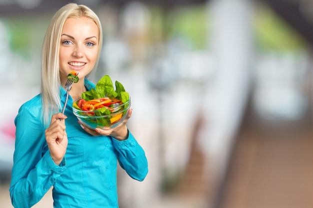 Retrato de una niña juguetona feliz comiendo ensalada fresca de un tazón