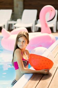 Retrato de niña de lado sosteniendo una pelota de playa