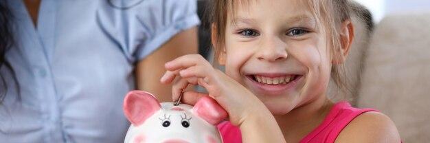 Retrato de niña linda arrojando ahorros en divertido hucha rosa. niño sonriente mirando a cámara con felicidad y alegría. concepto de ahorro de dinero