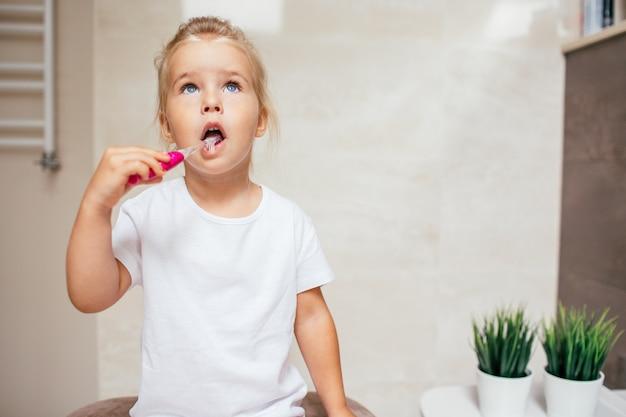 Retrato de niña linda con cabello rubio que diente de limpieza con cepillo y pasta de dientes en el baño. copyspace