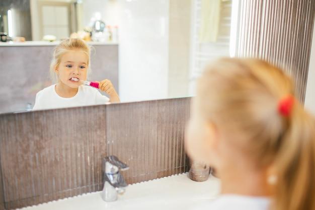 Retrato de niña linda con cabello rubio que limpia dientes con cepillo y pasta de dientes en el baño cerca del espejo.