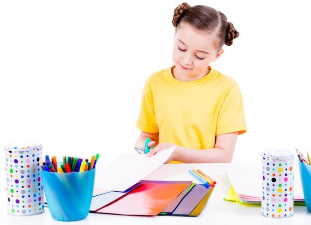 Retrato de niña linda en camiseta amarilla corta cartulina de tijera - aislado en blanco.