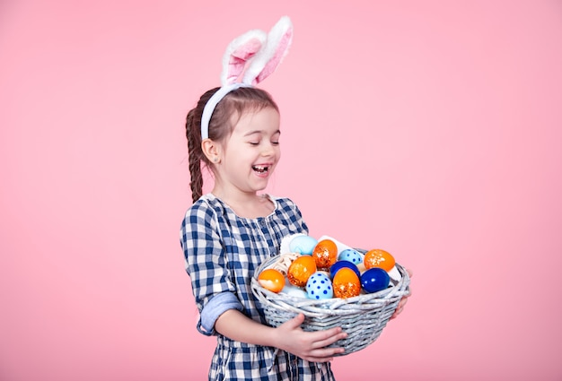 Retrato de una niña linda con una canasta de huevos de pascua en un fondo rosa aislado.