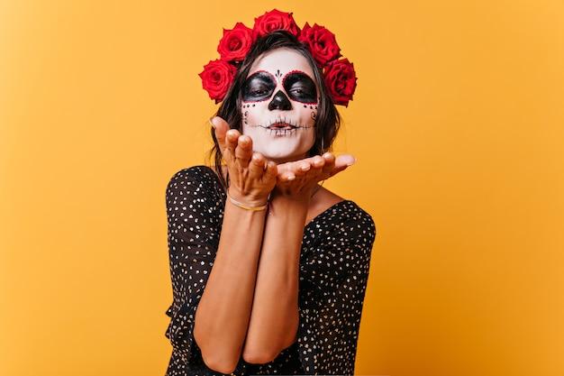 Retrato de niña linda con corona de rosas rojas, celebrando halloween. modelo en vestido negro está enviando beso al aire