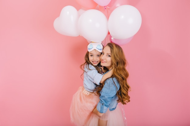 Retrato de niña linda del cumpleaños de pelo largo con globos blancos abrazando a su joven mamá rizada después del evento. encantadora madre posando con bonita hija en fiesta aislada sobre fondo rosa