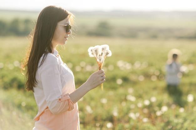 Retrato de una niña linda en un día soleado de verano en el fondo verde de la naturaleza