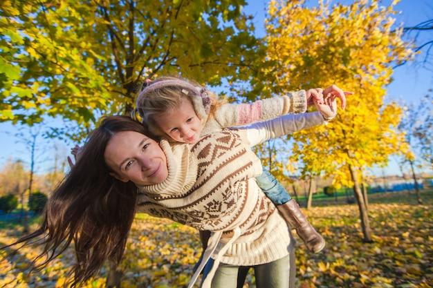 Retrato de niña linda y feliz madre divertirse en el bosque amarillo del otoño en un cálido día soleado