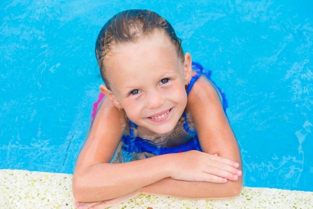 Retrato de niña linda feliz sonriente en la piscina al aire libre