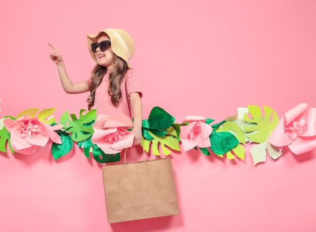 Retrato de niña linda con gafas y sombrero de verano, con bolsa de compras en mano sobre fondo rosa con flores de papel, lugar para texto, concepto de publicidad de verano