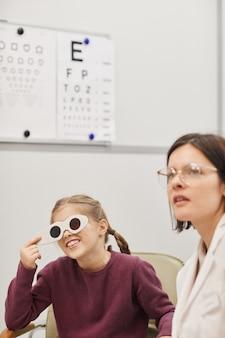 Retrato de niña linda leyendo la tabla de visión durante la prueba de la vista en la clínica de oftalmología pediátrica