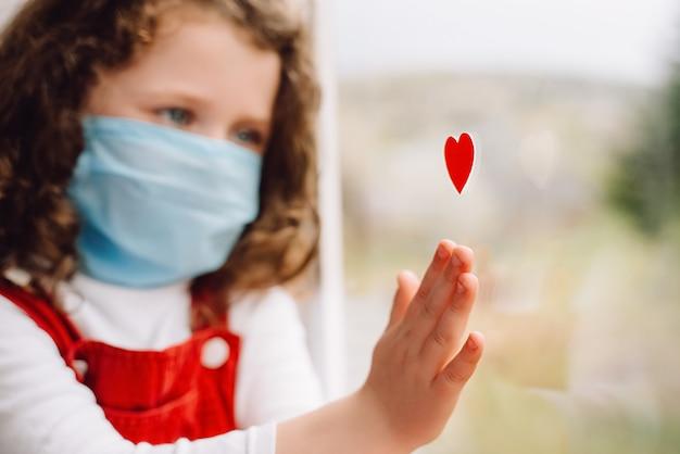 Retrato de niña linda con máscara médica con corazón rojo cerca de la ventana como una forma de mostrar agradecimiento a los médicos y enfermeras por su ayuda en la lucha contra la enfermedad. covid-19. enfoque selectivo