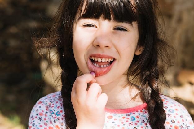 Retrato de una niña linda mostrando sus dientes rotos