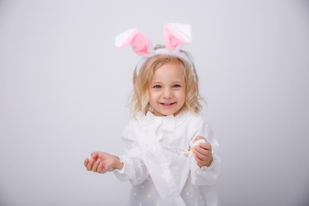 Retrato de una niña linda con orejas de conejo sobre un fondo blanco. felices pascuas