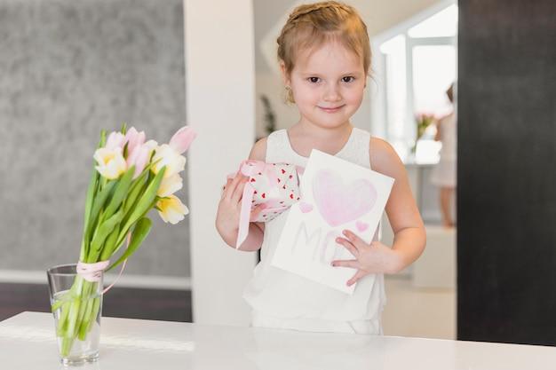 Retrato de niña linda de pie con caja de regalo y tarjeta de felicitación