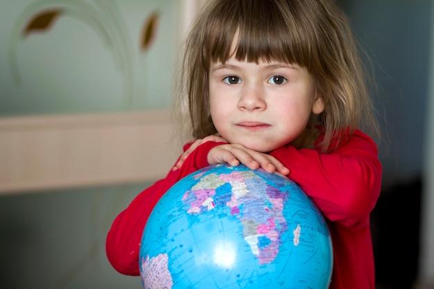 Retrato de la niña linda que abraza el globo de la tierra.