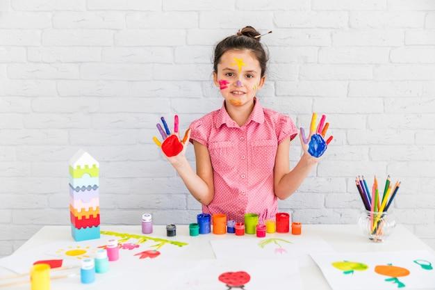 Retrato de niña linda que muestra sus manos pintadas de pie contra la pared de ladrillo blanco