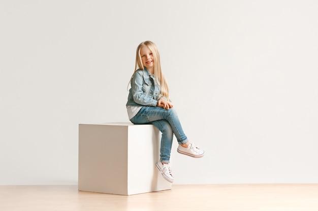 Retrato de niña linda con ropa de jeans con estilo mirando a la cámara y sonriendo, sentada contra la pared blanca del estudio. concepto de moda infantil