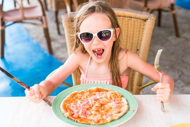 Retrato de niña linda sentada junto a la mesa y comiendo pizza