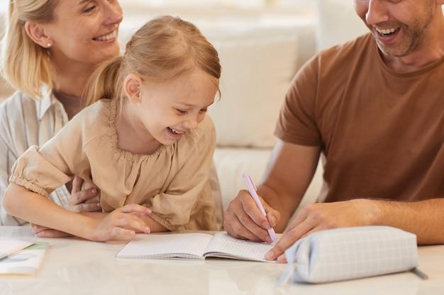 Retrato de niña linda sonriendo felizmente con los padres ayudándola a dibujar o estudiar en casa