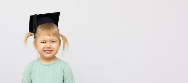 Retrato niña lleva sombrero de posgrado y sonríe con felicidad con espacio de copia para banner de concepto de educación