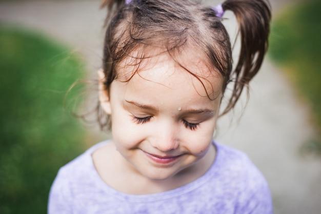 Retrato de una niña, lluvia, cabello mojado, caminando con su madre en el verano, coletas en la cabeza, sonrisa