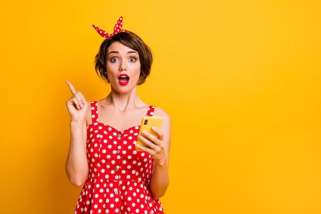 Retrato de niña loca asombrada usar teléfono inteligente charlando pensar pensamientos obtener una idea maravillosa levantar el dedo índice gritar wow dios mío usar traje de estilo vintage aislado brillo color pared