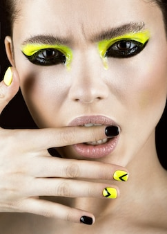 Retrato de niña con maquillaje amarillo y negro, diseño creativo de uñas. cara de belleza