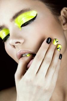 Retrato de niña con maquillaje amarillo y negro, diseño creativo de uñas