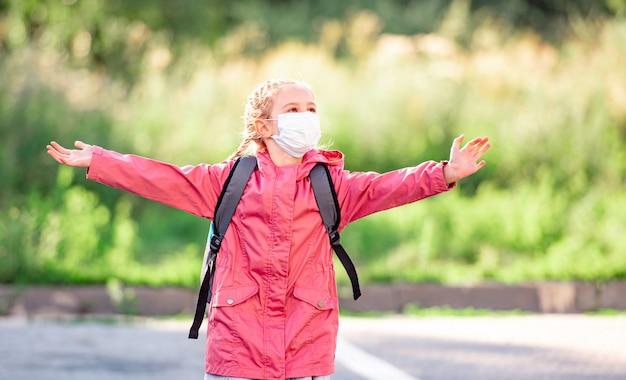 Retrato de niña con máscara corriendo al aire libre después de la escuela