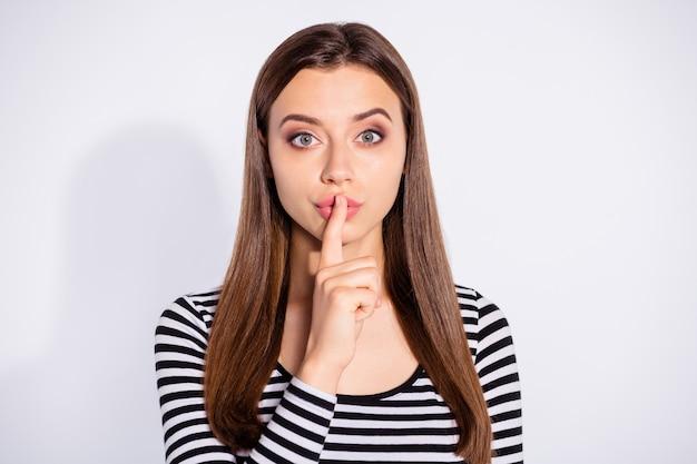 Retrato de niña de mente mirando con su dedo índice cerca de la cara vistiendo jersey de rayas aislado sobre la pared blanca