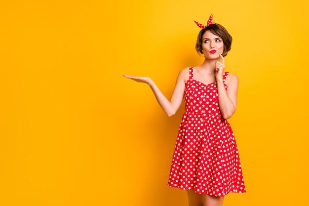 Retrato de niña de mente pensativa mantenga la mano opción de visualización anuncios promo pensar pensamientos inconscientes mirada insegura copyspace usar ropa de buen aspecto aislado pared de color brillante