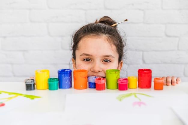Retrato de una niña mirando botellas de pintura de colores en el borde de la mesa blanca