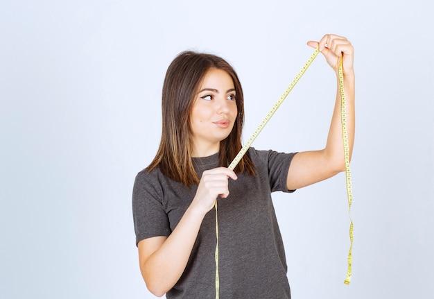 Retrato de una niña mirando una cinta métrica aislada sobre fondo blanco.