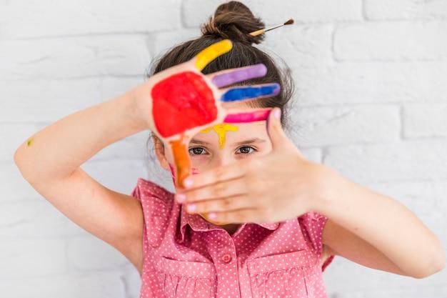 Retrato de una niña mirando a través de sus manos pintadas de pie contra la pared de ladrillo blanco