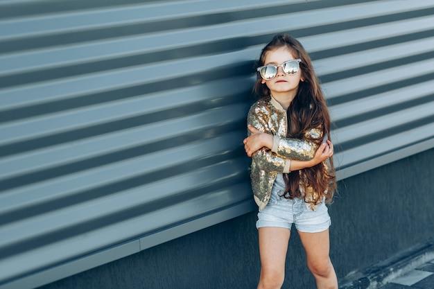 Retrato de una niña de moda contra la pared gris