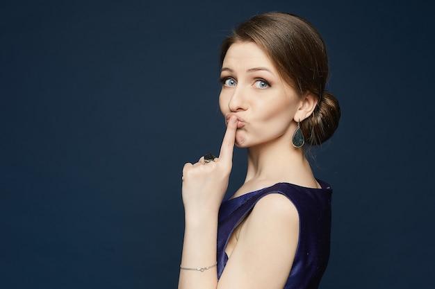Retrato de niña de moda modelo morena con ojos azules y vestido azul con el dedo cerca de la boca ...