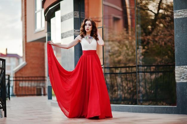 Retrato de niña de moda en el vestido de noche rojo que plantea la ventana de espejo de fondo del edificio moderno