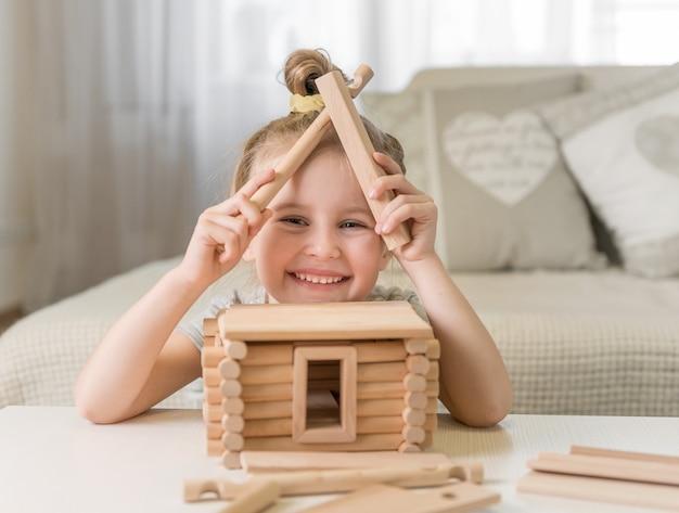 Retrato de niña con modelo de la casa.
