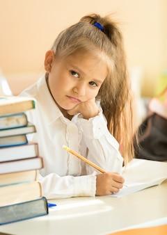 Retrato de niña molesta prueba de escritura en el aula y mirando a la cámara