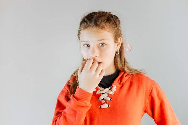 Retrato de una niña mordiéndose las uñas