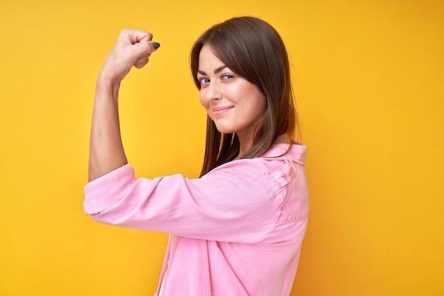 Retrato de niña morena feminista muestra fuerza, demuestra bíceps y mira a la cámara en amarillo. concepto de poder femenino